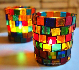 Two beautiful mosaic lanterns on a table.