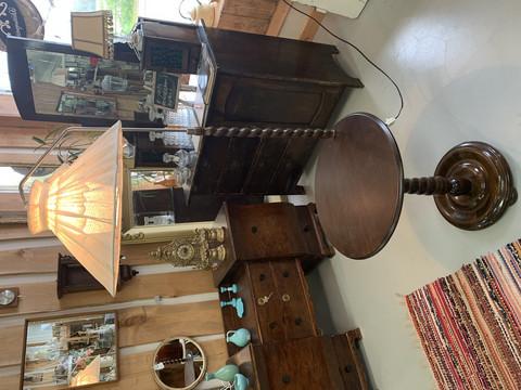 Vanha tummanruskea kierteinen jalkalamppu pöytätasolla, vanha valaisin