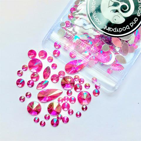 Erimuotoisia kirkkaanpinkkejä kimmeltäviä ihotimantteja