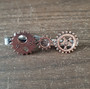 Steampunk tie clip with copper-colored gears.