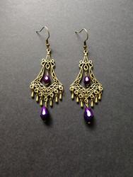 Roikkuvat pisarakorvakorut violeteilla helmillä