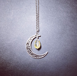 Crescent moon with yellow droplet
