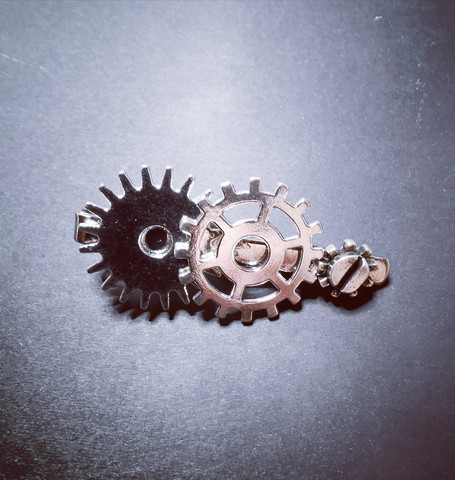 Silver-colored steampunk tie clip with gears.