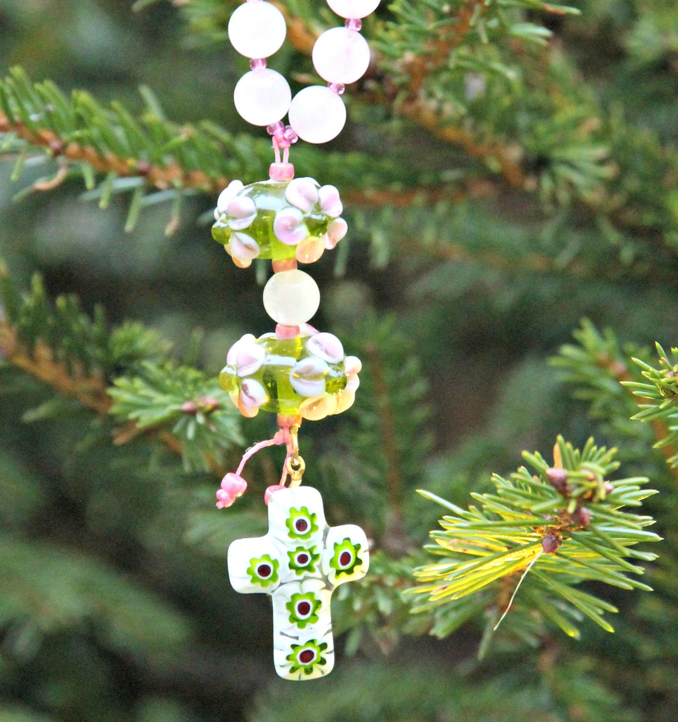 Titin uniikin rukousnauhan vihreä-pinkit lasihelmet ja risti roikkuvat kuusen oksalla