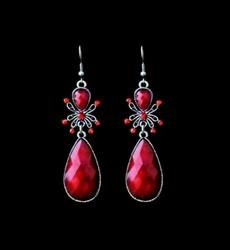 Punaiset korvakorut kimaltelevilla kristalleilla