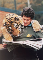 A tiger and a man are reading a newspaper