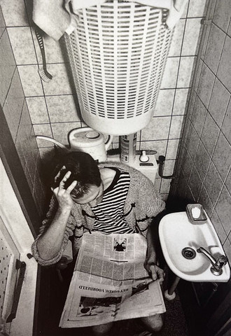 Man and newspaper in the toilet