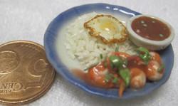 Nukkekodin ruoka: riisiä, paistettu kananmuna, simpukoita, dippikippo, sinireunaisella lautasella