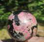Kivipallo eudialiitti jossa astrofylliittiä 690g 7cm  Katso video