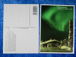 Postikortti Aurora Borealis. vihreät revontulet, puita  ja mökki