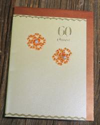 Postikortti ja kirjekuori: Onnea 60v, helmikukat punottu hopealangalla (a60v)