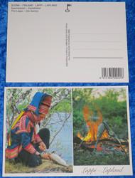 Postikortti Saamelaiset - mies perkaa kalaa ja kalat paistuu nuotiolla