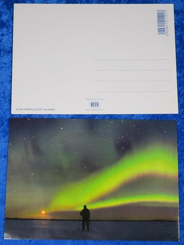 Postikortti revontulet, tähtitaivas ja hiihtäjä kuutamolla