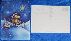 Joulukortti enkeli istuu poron pulkassa ja katselee tähtiä