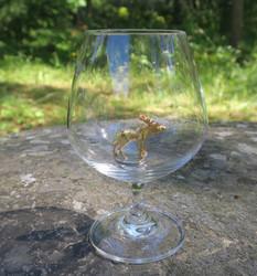 Konjakkilasi kullattu hirvi seisoo lasin pohjalla
