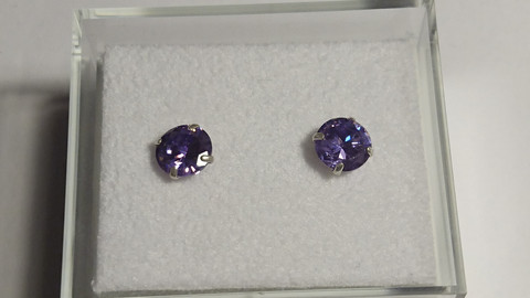 Hopeakorvakorut, pieni violetin värinen kivi