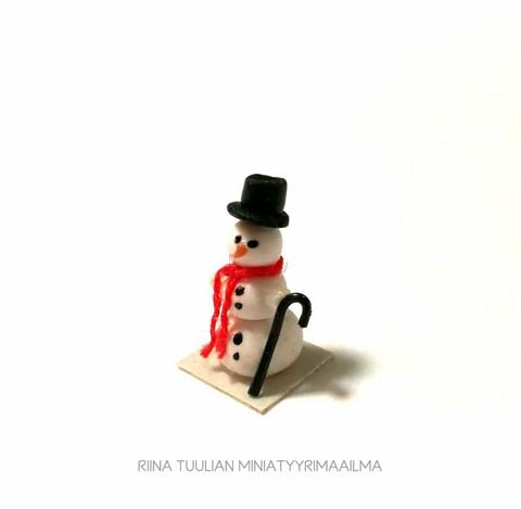 Miniatyyri Lumiukko -koriste jalustalla